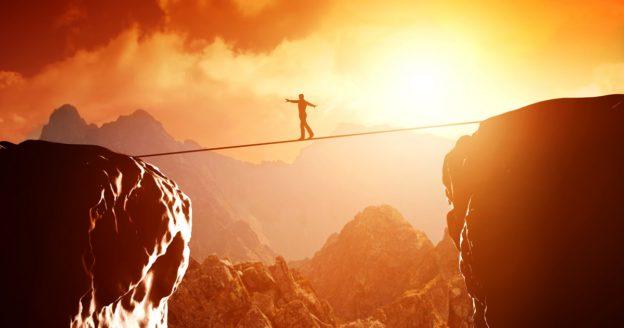 Mut: Mensch balanciert über Schlucht